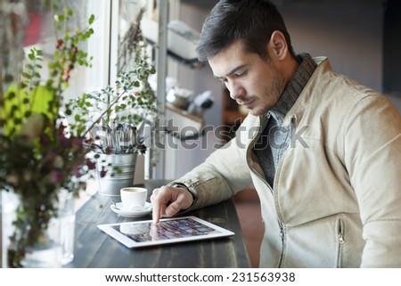 Handsome Man Using Tablet Computer Indoor - stock photo