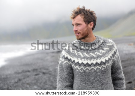 Handsome man walking black sand beach on Iceland wearing Icelandic sweater. Good looking male model looking pensive at ocean sea. - stock photo