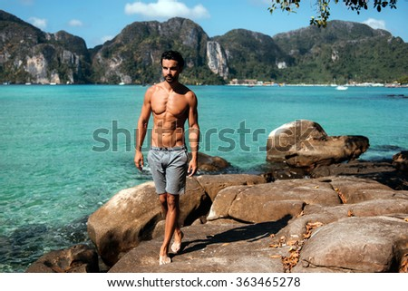Handsome man walking on the rocks on the sea view. Gym handsome brunette hair man with nude torso on the beach in Phi Phi island, Thailand