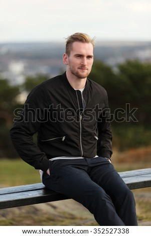 Handsome man wearing a black jacket and jeans sitting down outside on a bench on a cold windy autumn day.