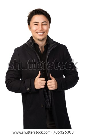 Handsome man wearing a warm black jacket, looking at camera with a big smile on his face. Standing against a white background.