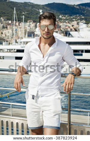 Handsome man wearing aviator sunglasses and posing in port - stock photo
