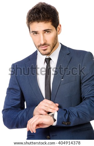 Handsome man wearing elegant suit looking at his wristwatch. Time concept. Men's beauty, fashion. Isolated over white.