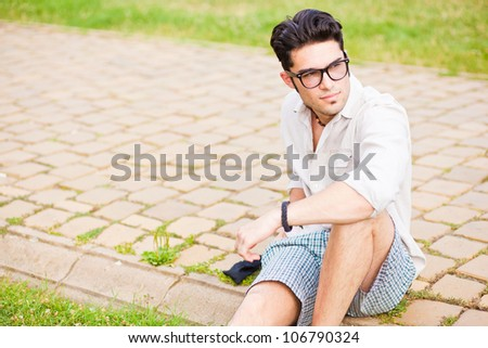 handsome man wearing glasses sitting on the sidewalk looking away - stock photo