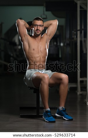 Handsome Man Wearing Glasses Working Out Triceps With Dumbbell In A Dark Gym