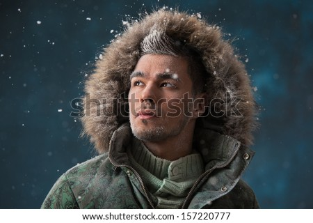 Handsome man wearing jacket with fur hood in winter snow at night