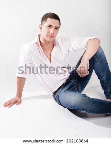 Handsome man wearing jeans and shirt sitting on floor