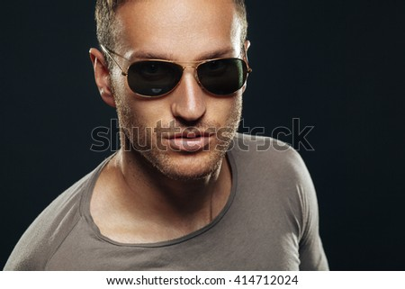 Handsome man wearing sunglasses in the studio on a dark background - stock photo