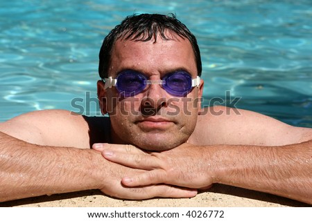Handsome man wearing swim goggles in the pool