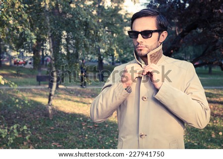 Handsome man wearing trench coat in park, vintage style - stock photo