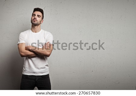 Handsome man wearing white blank t-shirt with white grunge wall on background - stock photo