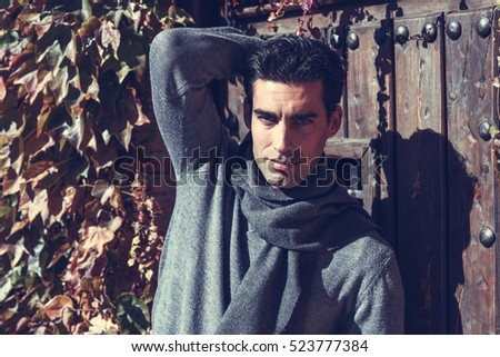 Handsome man wearing winter clothes in autumn leaves background. Young male with sweater and scarf.