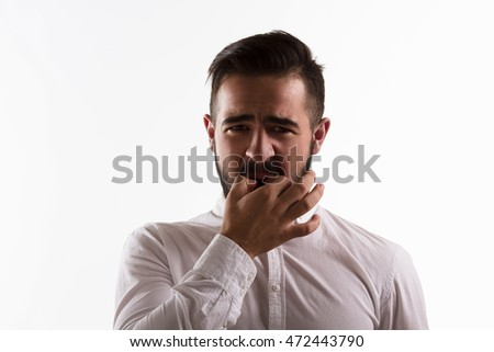 Handsome man whistling isolated on white background. Brunette hipster man in white shirt posing in studio. Emotions concept. Hardlight lightening concept.