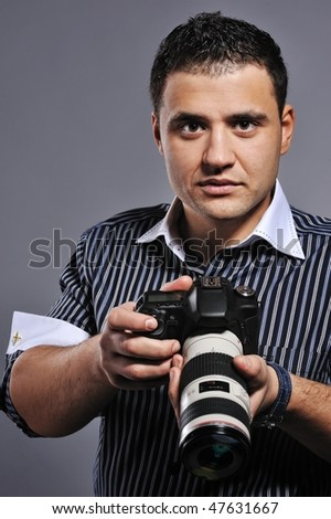 Handsome man with a digital camera - stock photo