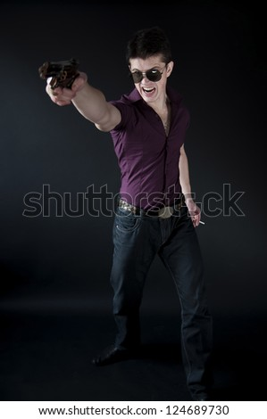 handsome  man with a gun wearing black glasses - stock photo