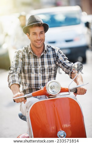 handsome man with a hat riding a vintage scooter in the street - stock photo