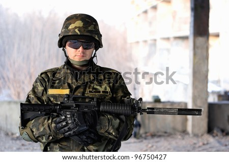 Handsome man with a rifle in front of neglected house
