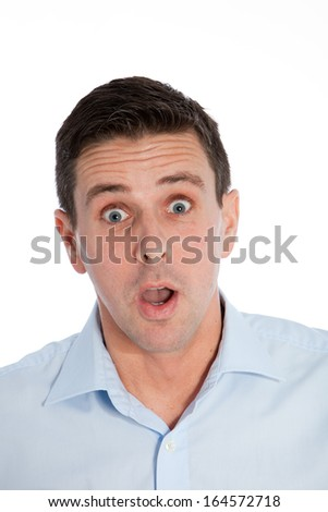 Handsome man with a startled expression of awe and amazement staring wide eyed at the camera with his mouth open, isolated on white