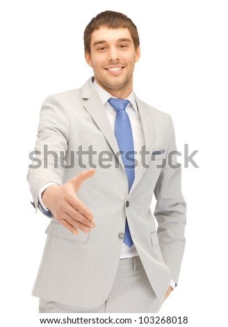 handsome man with an open hand ready for handshake - stock photo