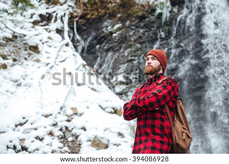 Handsome man with backpack standing near a waterfall outdoors and looking away - stock photo