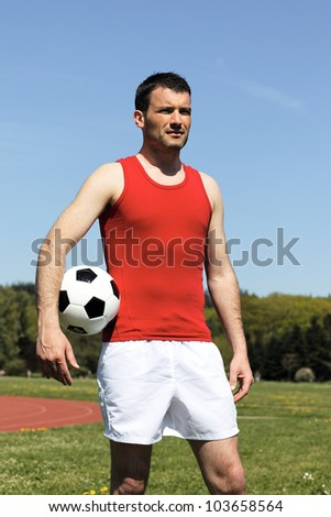 handsome man with ball under the arm - stock photo