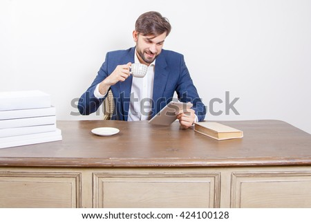 Handsome man with beard and brown hair and blue suit and tablet and some books and cup drinking coffee or tea sitting in the office holding tablet and smiling.  Isolated on white background. - stock photo