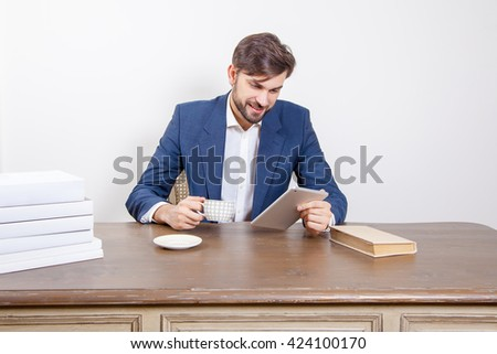 Handsome man with beard and brown hair and blue suit and tablet pc computer and some books and cup drinking coffee or tea sitting in the office holding tablet and smile.  Isolated on white background. - stock photo