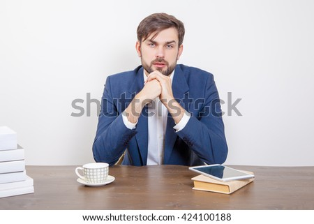 Handsome man with beard and brown hair and blue suit and tablet pc computer and some books sitting in the office looking at camera with serious face.  Isolated on white background.   - stock photo