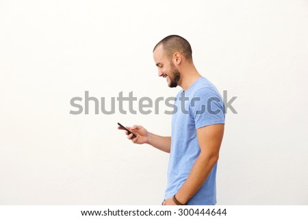 Handsome man with beard walking with mobile phone against white background - stock photo