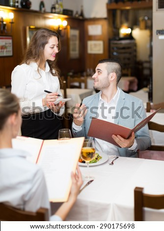 Handsome man with beautiful girlfriend making order at cafe  - stock photo