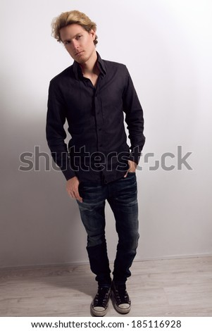 Handsome man with blonde hair, dressed in black shirt, blue jeans and sneakers, with hands in his pockets, looking at camera - stock photo