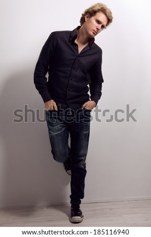 Handsome man with blonde hair, dressed in black shirt, blue jeans and sneakers, with hands in his pockets, standing near the wall and looking away - stock photo