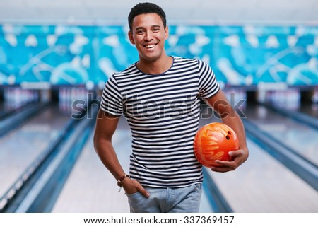 Handsome man with bowling ball looking at camera