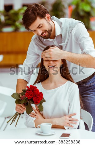 Handsome man with bunch of red roses covering his beautiful woman eyes while meeting her in cafe