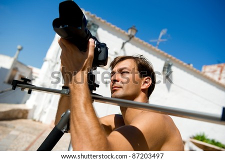 Handsome man with camcorder outdoors - stock photo