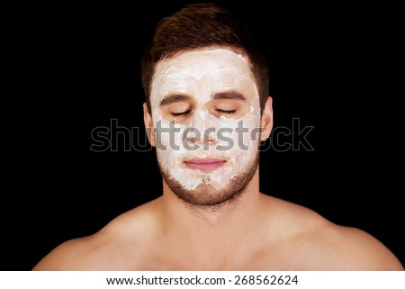 Handsome man with cream moisturizer on his face. - stock photo