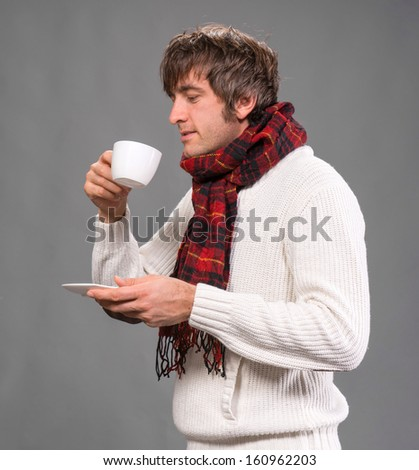 Handsome man with  cup of hot coffee or tea on a gray background