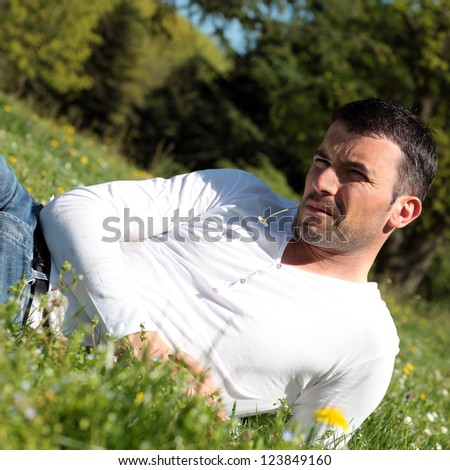 handsome man with daisy in a park - stock photo