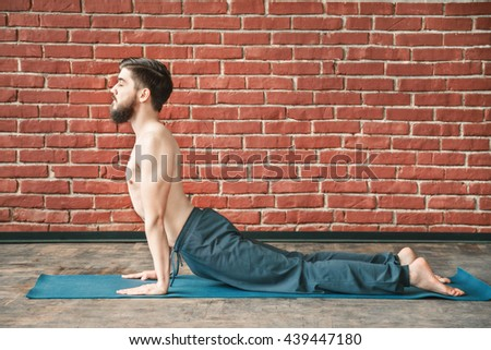 Handsome man with dark hair and beard wearing trousers doing yoga position, closed eyes,  on blue matt at wall background, copy space, portrait, closed eyes, cobra pose bhujangasana asana. - stock photo