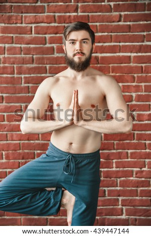 Handsome man with dark hair and beard wearing trousers doing yoga tree position on blue matt at wall background, copy space, portrait, vrikshasana asana. - stock photo