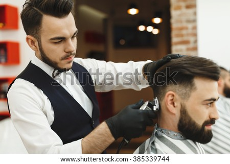 Handsome man with dark hair wearing white shirt doing a haircut for man with black hair at barber shop, copy space, close up.
