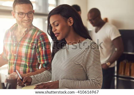 Handsome man with eyeglasses and beautiful woman in striped long sleeve shirt working at desk with co-workers in background