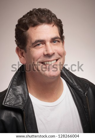 Handsome man with friendly smile in black leather jacket - stock photo