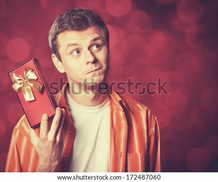 Handsome man with gift. Photo with bokeh at background. - stock photo