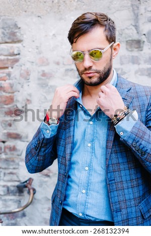 Handsome man with glasses ina suit, against old vintage wall, outdoors. - stock photo
