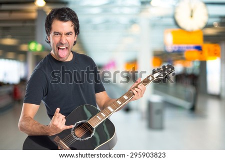 Handsome man with guitar on unfocused background