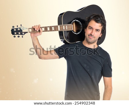 Handsome man with guitar over ocher background - stock photo