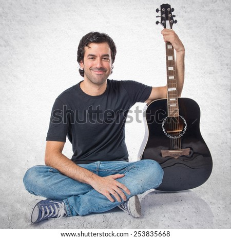 Handsome man with guitar over textured background - stock photo