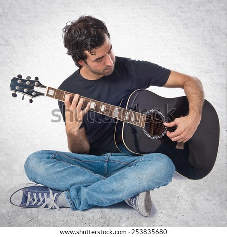 Handsome man with guitar over textured background