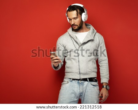 handsome man with headphones looking at smart phone  - stock photo